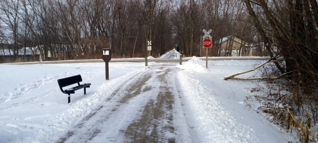 Image of trail with snow and stop sign