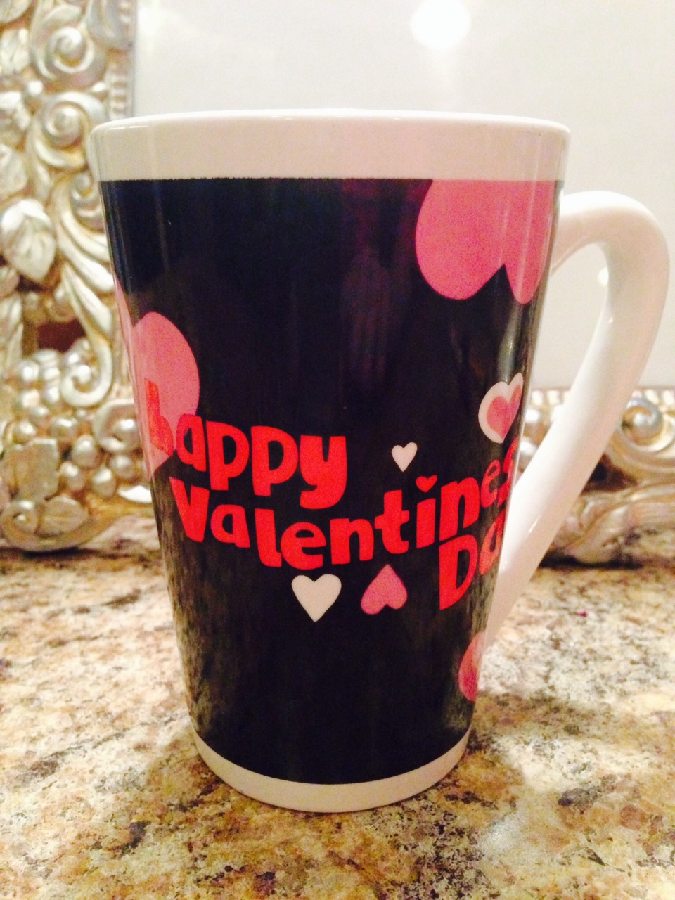 "Black coffee cup with pink hearts that says, ""Happy Valentine's Day."""