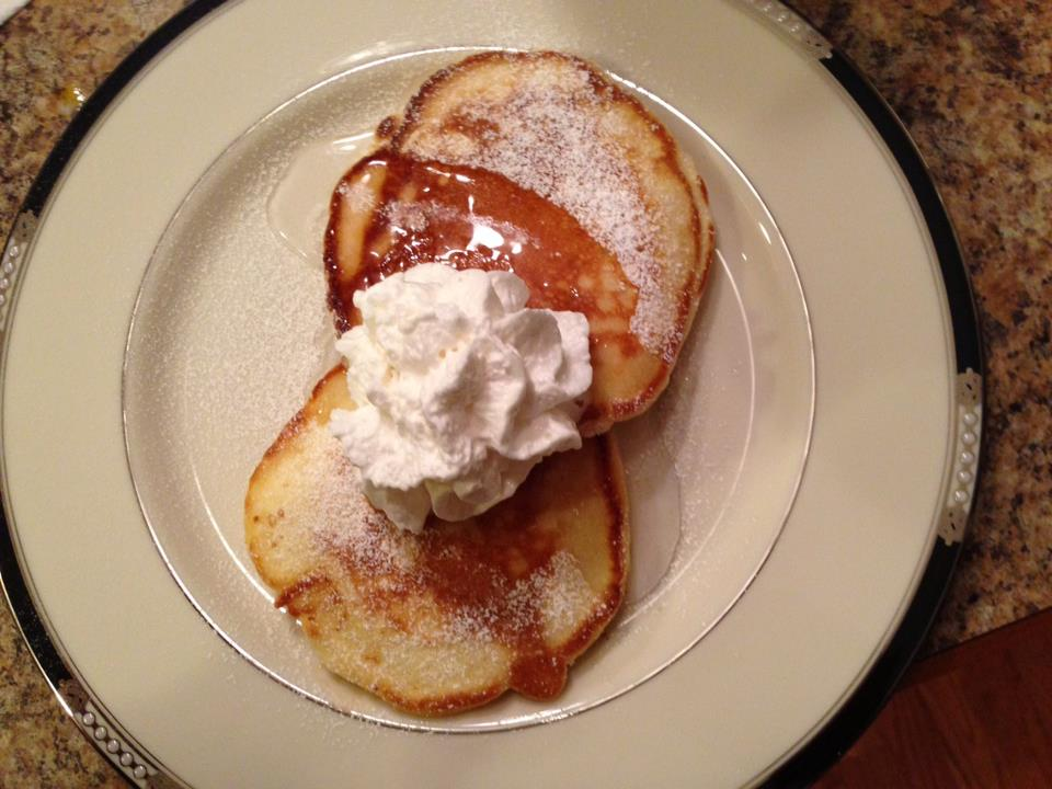 image of pancakes dusted with powdered sugar with whipped cream on them