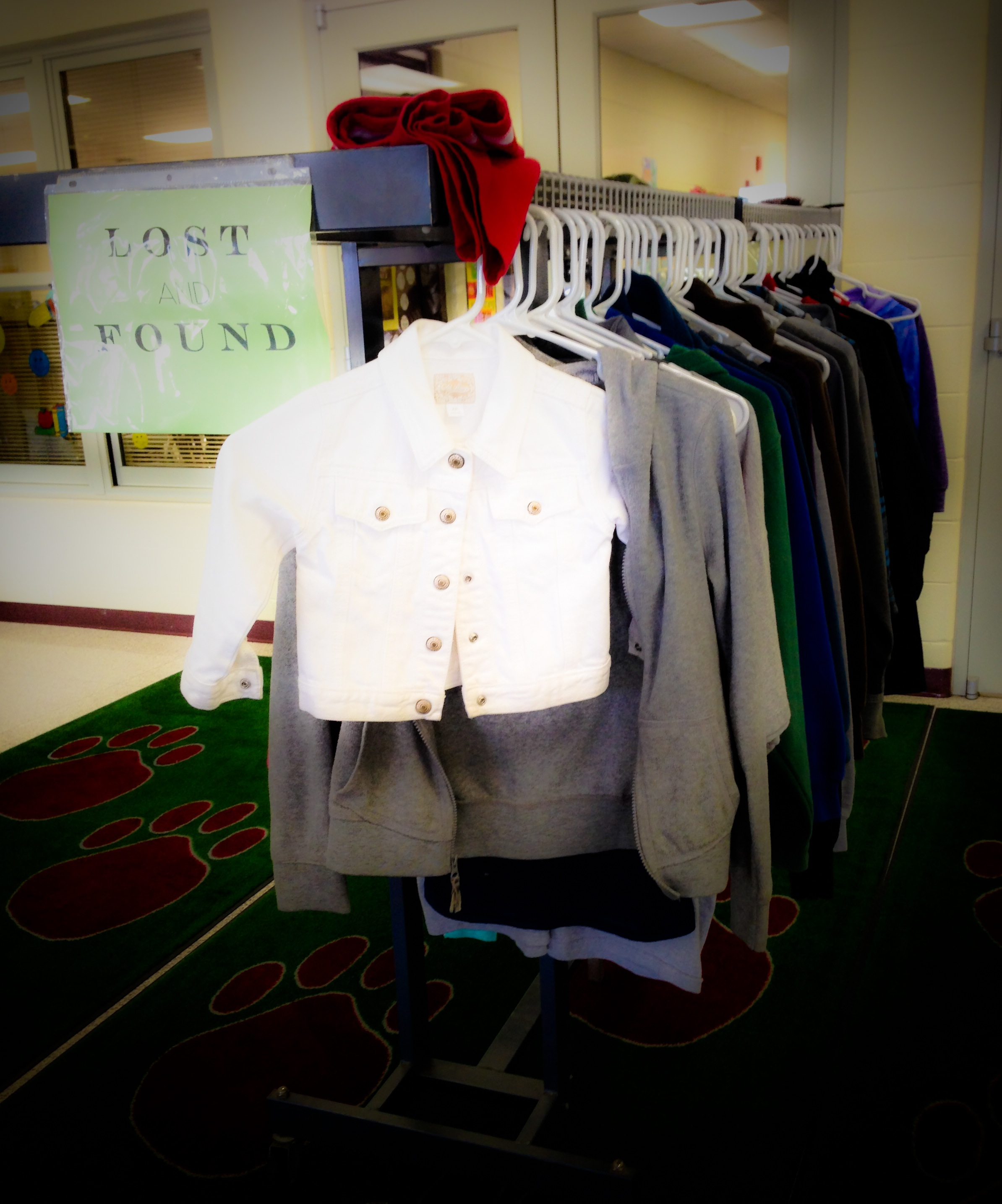 Small white child's jacket hung on a lost and found rack at school with other larger clothing items.
