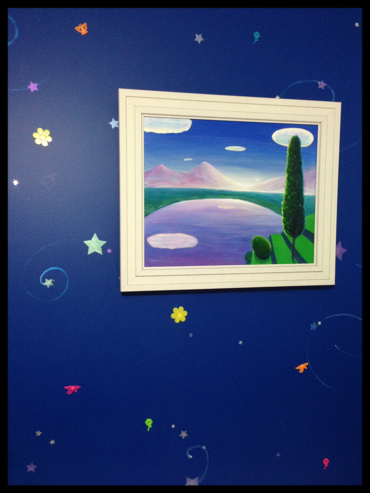 Blue wall with painting hanging on it and stars pained on a dark blue wall.