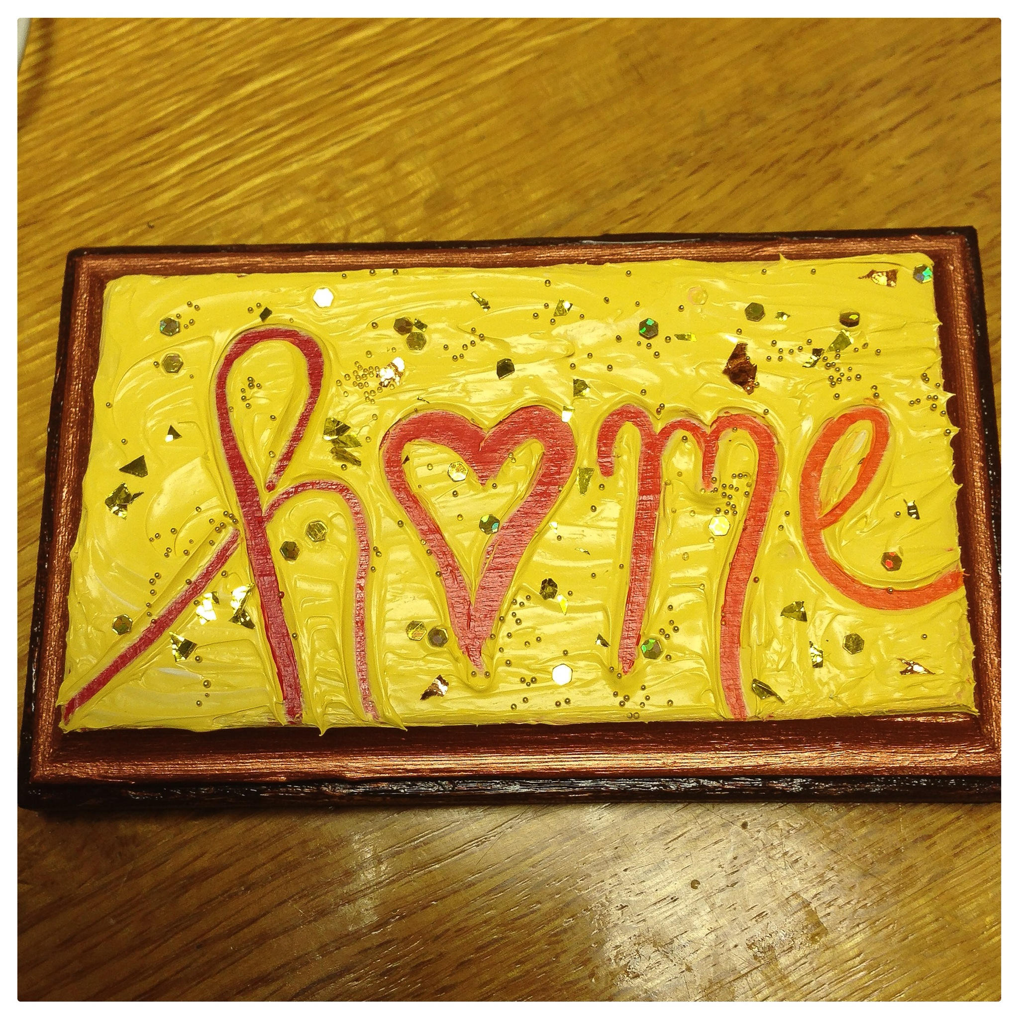 Painted plaque with the word home on it.