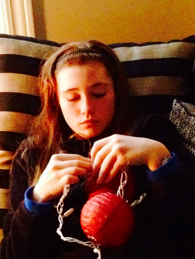 Daughter assembling the paper lantern lights for The Giving Tree Project.