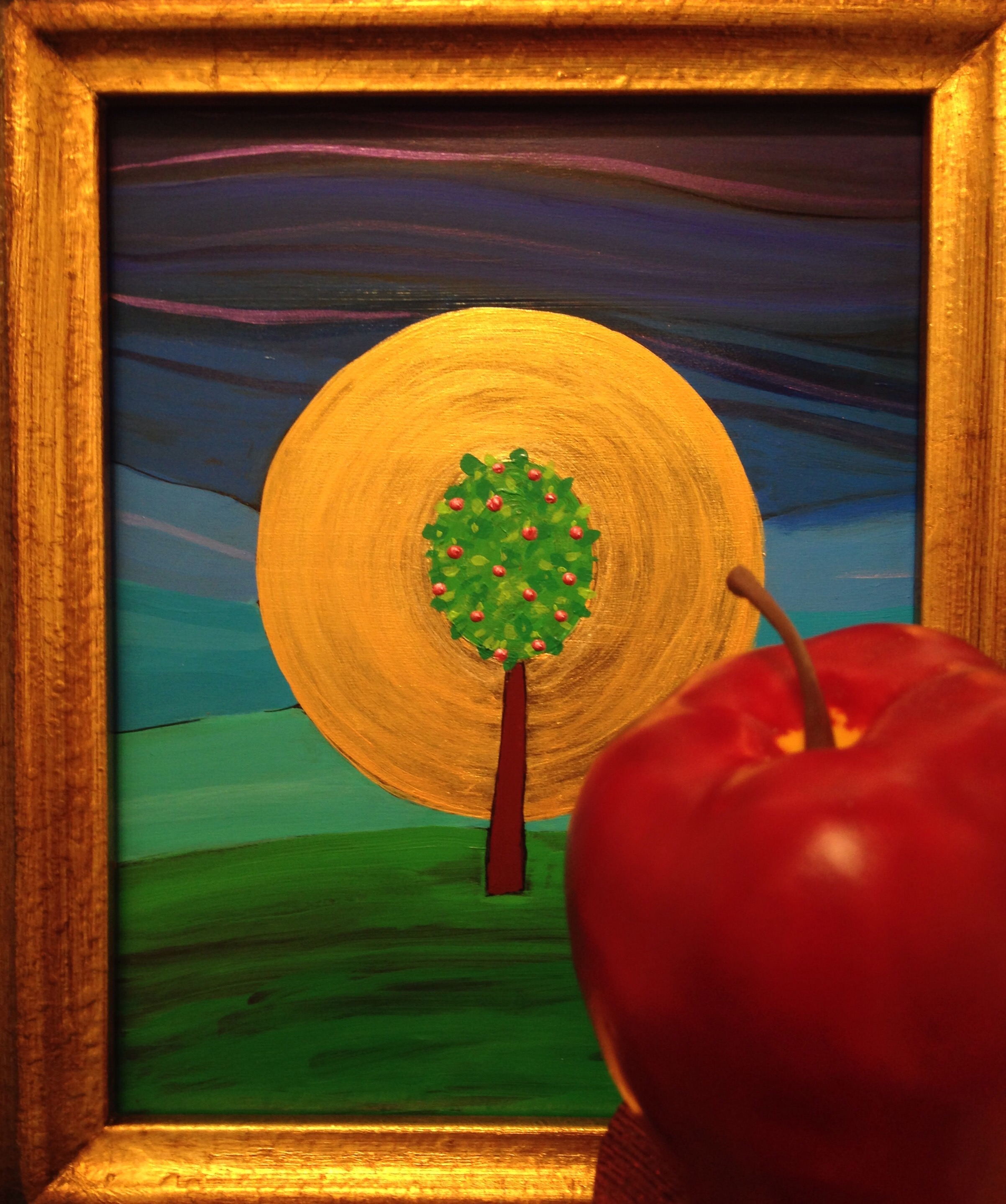 Painting of The Tree of Life by Angel Ambrose and an large red apple.