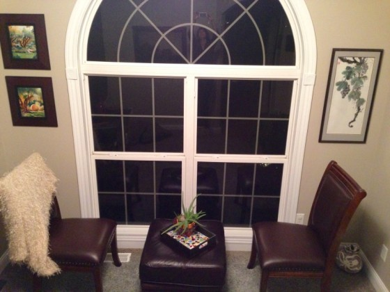 Two chairs in front of an arch window.