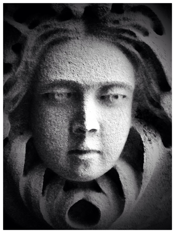 A stone portrait of a woman gazing outwardly.